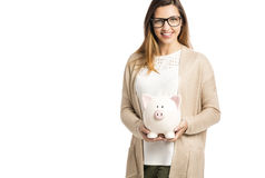Woman holding piggybank. Beautiful and happy woman holding a piggy bank, isolated over white background Stock Photos