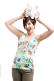 Woman holding a piggybank over her head. Beautiful happy woman holding a piggybank over her head, isolated over a white background Stock Photos