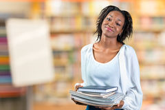 Woman holding a pile of books. Young african woman holding a pile of books Stock Photography