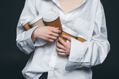 Woman holding pile of disposable coffee cups. Mid section of woman holding a pile of disposable coffee cups, studio shot Royalty Free Stock Photography