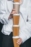 Woman holding pile of disposable coffee cups. Mid section of woman holding a pile of disposable coffee cups, studio shot Stock Photos