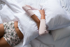 Woman holding pillow on bed. Woman holding pillow while relaxing on bed at home Royalty Free Stock Photo