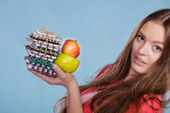Woman holding pills and fruits. Health care Stock Photos