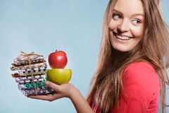 Woman holding pills and fruits. Health care Stock Image