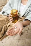 Woman holding pills and glass. Royalty Free Stock Photo