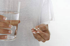 Woman Holding Pills And Glass Of Water Stock Images