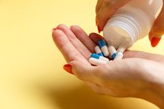 Woman holding pills on hand royalty free stock images