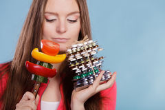 Woman holding pills and vegetables. Health care Stock Image