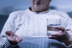 Woman holding pills and water Stock Images