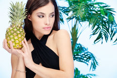Woman holding pineapple. In front of a palm tree Stock Images