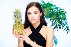 Woman holding pineapple. Pretty woman holding pineapple in front of a palm tree Stock Images