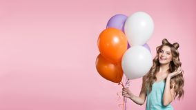 Woman holding pink balloons over pink background. stock images