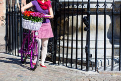 Woman holding pink bike. With basket full of flowers on the street of an old town in Gdansk, Poland royalty free stock photo