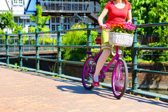 Woman holding pink bike. Woman holding and starting to ride pink bike on the on the street of an old town in Gdansk, Poland stock photo