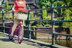 Woman holding pink bike. Woman holding and starting to ride pink bike on the on the street of an old town in Gdansk, Poland, vintage colors stock photos