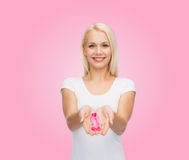 Woman holding pink cancer awareness ribbon. Healthcare and medicine concept - smiling woman in blank t-shirt holding pink breast cancer awareness ribbon royalty free stock photography