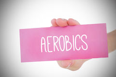 Woman holding pink card saying aerobics. Against white background with vignette Stock Images