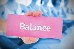 Woman holding pink card saying balance Royalty Free Stock Images