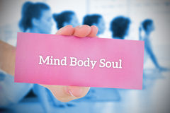 Woman holding pink card saying mind body soul. Against yoga class in gym stock photo