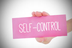 Woman holding pink card saying self control. Against white background with vignette royalty free stock photos