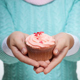 Woman holding a pink cupcake on white Royalty Free Stock Photos