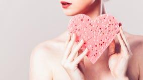 Woman holding pink heart sponge in hands. Stock Photos