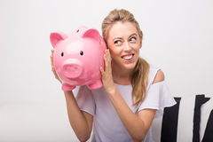 Woman holding pink piggy bank next to her ear Stock Images