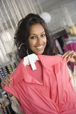 Woman Holding Pink Sleeveless Top. Portrait of happy Indian women selects pink sleeveless top in clothes shop Stock Image