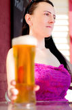 Woman holding a pint in beer garden portrait Royalty Free Stock Images
