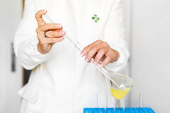 Woman holding pipette and flask Stock Photos