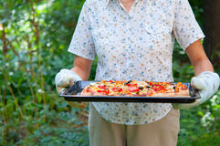 Woman holding pizza tray Stock Photography