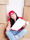 Woman holding plan of house sitting with cartons Royalty Free Stock Image