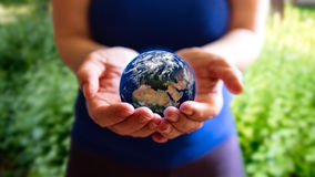 Woman holding planet. A woman holding the Earth in her hands. Earth textures courtesy of NASA/JPL-Caltech Royalty Free Stock Photography