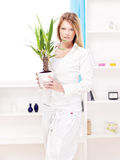 Woman holding plant in pot at home Stock Photos