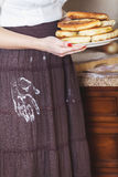 Woman is holding plate of cakes, flour skirt handprint Stock Image