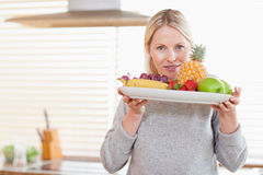 Woman holding a plate of fruits Stock Photos
