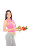 Woman holding a plate full of vegetables Stock Photography