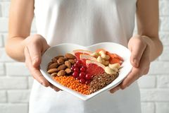 Woman holding plate with products for heart-healthy diet. Closeup royalty free stock image