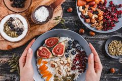 Woman holding plate of Rice coconut porridge with figs, berries, nuts and coconut milk on rustic wooden background. Healthy breakfast ingredients. Clean eating stock photo