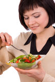 Woman holding plate with salad and eating. Royalty Free Stock Photo