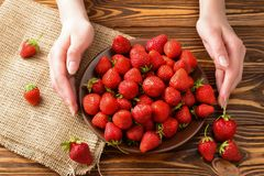 Woman holding a plate of strawberries. royalty free stock photography