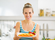Woman holding plate with strawberry and orange Stock Photos