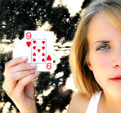 Woman holding playing card. A young woman holds up a nine of hearts playing card. Half her face has been cropped out of the picture. The background is a black stock photography