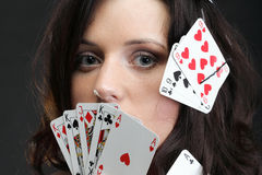 Woman holding playing cards black background Stock Photos