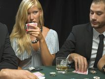 Woman holding playing cards in poker game Royalty Free Stock Photos