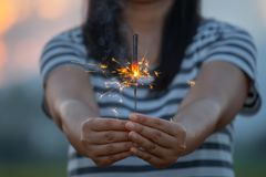 Woman holding and playing with fire sparklers on the festival royalty free stock photography
