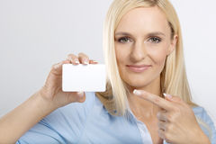 Woman holding and pointing to card Stock Photos