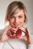 Woman holding pomegranate. Studio shot of beautiful young adult holding pomegranate Stock Photos