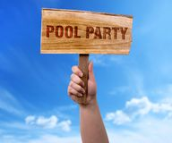 Pool party wooden sign. A woman holding pool party wooden sign on blue sky background Stock Photo