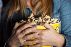 Woman Holding Popcorn Bucket In Theater Stock Photo